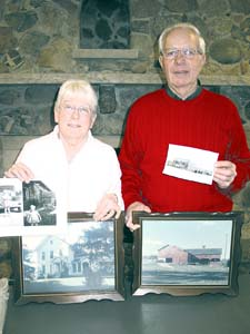 DEEP ROOTS - Barb (Ammerman) Stevens is pictured with Gene Berry holding pictuers of the past. Berry shared the history of both families at last month's