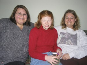 "THE NEXT STEP-Kailey Sturr, center, is pictured with two of her caregivers, Anissa Olinger and Jennifer Wrobleski, on the couch in ""Kailey's House."""