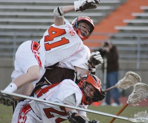 Brandon Emmons (#41) goes airborne after an illegal push from behind by a Holt player, as he and Nicky Howard (#24) fight to gain possession of the ball after a face-off.Photo by SUE POUBA