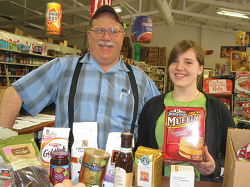 BARGAINS GALORE—Roger Anderson with his daughter Bethany, 15, show off some of the gourmet products the store sells at deliciously low prices.