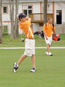 Rockford's Steven Mette tees off at Stonegate Golf Club, while team captain Adam Hoard stands by.