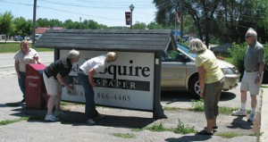 """FINDING IS FUN—Geocaching at the Squire are three generations, including visitors from Massachusetts. A mom, dad and three sisters, one with her two children were """"caught"""" geocaching outside the Squire on Thursday, July 16. Beth (""""Just Fiddling Around"""" to geocaching friends) along with son and daughter Andrew and Hillary Baning came a long way to make this find. They were visiting with Beth's sister Mary """"Merry Mountainbiker"""" from Hudsonville, Nancy """"Nine Patch Nancy"""" from Rockford, and their mom and dad, Edwin and Alma Walhout """"EdAlma"""" of Grand Rapids."""