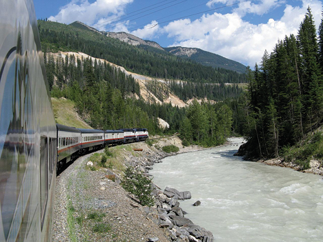 ALL ABOARD!—Squire photographer Cliff Hill hangs from an observation platform to capture this picture of the Rocky Mountaineer Train en route