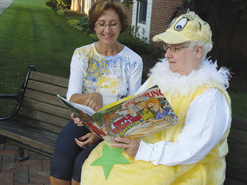THE THINGS YOU HAVE TO DO AS MAYOR—Include dressing silly to promote the town's newest festival, Reading Rocks in Rockford. Mayor Chi Chi Rogers reads with Rockford Rotary president Ramona Hinton. As part of Hinton's presidency, she came up with this new festival to promote literacy in an active, hands-on way.