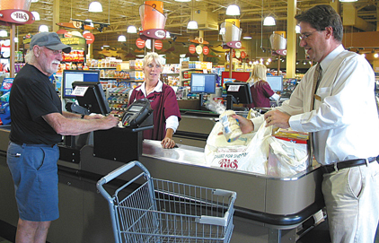 HAPPY CUSTOMER—Ric's Food Center Store Director Dave Brickner bags groceries for a customer at the store. Brickner counters rumors about the store due to the stalled development nearby.