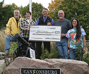 HIDDEN TREASURE FOUND—Treasure hunt organizers are pictured with the Grattan man who found the coin here. From left are Dennis Spitler, Linda Anderson, Carl Stites, Joe Longo and daughter Kristen. Kristen said she will get to spend some of the $1,000 in free gas whether her dad knows it yet or not.