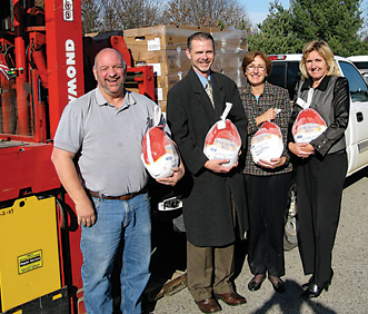 ROTARY TURKEYS HOLD SPARTAN TURKEYS—Seriously, though, North Kent Service Center (NKSC) warehouse manager John Leale (left) and NKSC office manager Deb Slot (right) receive a generous donation of 116 D&W Fresh Market turkeys from the Rockford Rotary Club, represented by past president Dave Robach (center left) and current president Ramona Hinton (center right).