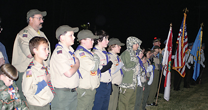 Local Boy Scouts stand with their hands on their hearts during the playing of taps and a gun salute by the Sons of the American Legion Post 258 Color Guard.
