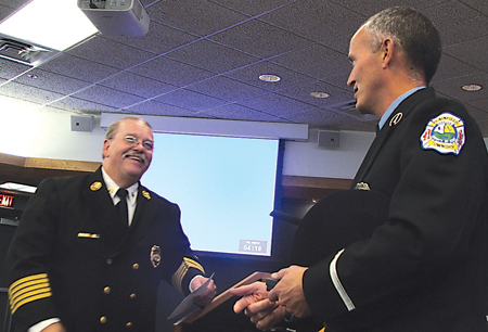 WITH THANKS—Fire Chief David Peterson congratulates Lt. Jeff Drake as he receives honors for his years of service with the department.