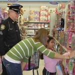 COPS CAN SHOP—But daughters are better. Here officer Mike Miller, shopping for Ruby, is helped by his daughter Stacie.