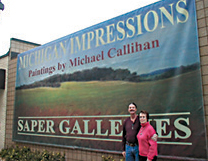 Michael Callihan and his wife in front of a banner announcing his gallery.