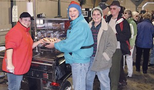 """Finishing the Resolution Walk, trekkers line up for hot dogs, including Polish and Italian—with every imaginable trimming—served up by """"Coney Girl"""" Jennifer Idema. Two happy campers receiving a plateful are Jerry and Ann VanDusen of Rockford's Bella Vista neighborhood.Photo by CLIFF HILL"""