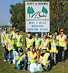 Several Rockford Christian School sixth-grade students and parent volunteers pick up trash from the roadside in September.