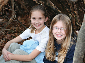 Kaylie Chiles and Ashley Solle, sixth-graders at RCS, sit inside Chiles' survival shelter in November.