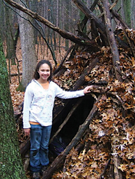 RCS sixth-grader Hannah Collins shows her winter survival shelter at Camp Roger.