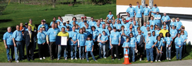 Posing for a group photo are a sea of blue clad Comcast volunteers ready to invade  the Fred Meijer White Pine Trail. Pictured in the fr