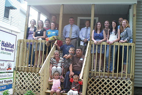 UNSTOPPABLE—Members of Rockford Youth Initiative, school officials and the Cisneros family stand on the porch of the home the students bought from the City of Grand Rapids and rehabbed for Habitat for Human