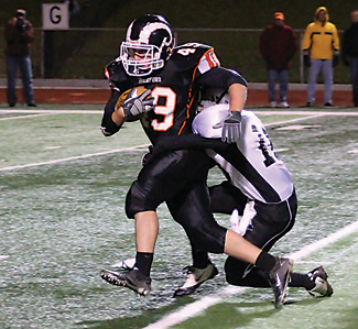 Brady Gent plows through the West Ottawa defense for 152 yards and three touchdowns.	Photo by JIM COOPER