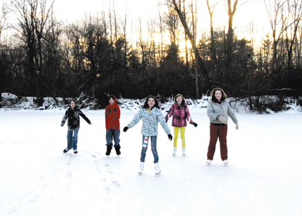 As the sun sets in the west, (pictured l–r) twin brothers Ben and Alex Norkey, 12, Bridgette Davis, 12, Grace Garner, 12, and Lexi Loop 12, all North Rockford Middle School students, are having a blast. They have been skating on the pond regularly since