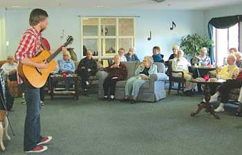 """On March 24 at 6 p.m. Jon Troast, singer/songwriter, gave a one-hour performance for about 45 residents and family members at Meadowlark Retirement Community. Troast traveled from Nashville, Tenn. to perform this concert. Jon's website is Jontroast.com. Troast said he used to dislike Mr. Rogers' song """"I Like to Take My Time,"""" but now has a different attitude. """"As funny as it might sound"""