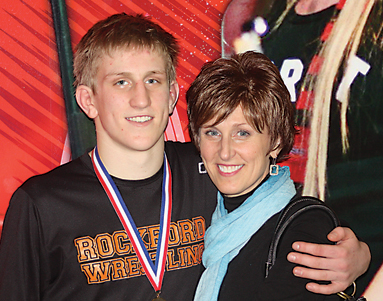 Austin Scogg poses with his mother Renee after winning the 152-pound state championship in Divi