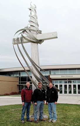 A JOB WELL DONE—with beaming faces (l–r) Cornerstone Head Lay Leader Ken Watkins, sculptor Steve Anderson, and Kent Companies COO and church member Dave Turner stand before the completed