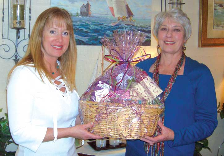 Christine Gault of A Charmed Life andPolly VonEschen of Baskets in the Belfry shows off the prize package that one lucky winner will receive from a Girlfriend