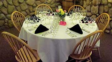 Six wine glasses radiating  spoke-like from the table's center await each guest prior to seating.