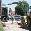 THIS IS HOW MEN VACUUM—Crews from Advanced HydroAir and Rockford's Department of Public Services (DPS) remove water and mud from a hole DPS dug to reach a damaged service main.
