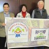 Rockford City Manager Michael Young, Rockford Farm Market organizer Kim McKay, and Market Master Lion Bob Winegar proudly hold the America's Favorite Farmers Market banner that will be on display Saturday mornings at Rockford's Farm Market.	Photo by CLIFF HILL