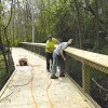 Finishing touches – (L to R) Justin and Cody Bultsma of Bultsma Construction installing low maintenance vinyl coated chain link fencing on the final segment of the Rogue River Nature Trail.Photo by CLIFF HILL