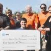 Mitchell Peterson (front) holds the AT&T donation check of $5,000. He is surrounded by (l–r) Pete MacGregor, Mimi Wyatt, Kristen Ha
