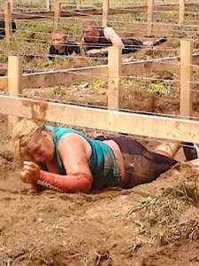 Rockford Squire writer Cindy Cranmer was among the 43 women on the Dirty Girl Scout team who successfully completed the Tough Mudder. Cranmer is pictured here army crawling under barbed wire and through mud and water at the Kiss of Mud obstacle. Photo courtesy of family and friends of the Dirty Girl Scouts.