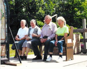 Left to right, seated on the church pew pulled by horse and wagon are Sister Angela Brocca MC, Sister Felicia Bertaina MC, Louis Gryka, Mrs. Aggie Zemke.