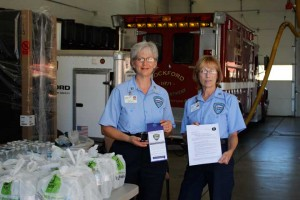 Robin Behrend and Becky Matson show off material provided by the Kent County Health Department on Thursday, September 5 in the fire station at Rockford City Hall. The pair were among a number of Department of Public Safety volunteers who handed out free bottled water during a boil advisory for the residents of Rockford.